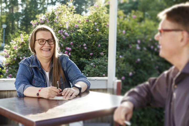 Riitta Mikkonen istumassa pöydän ääressä, kädessään kynä ja haastattelulehtiö. Vastapäätä häntä istuu haastateltava mieshenkilö.