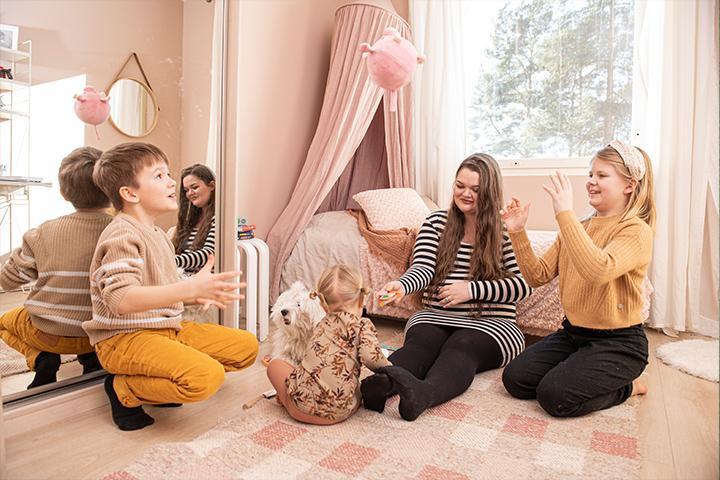 Emilia Huttunen kolmen lapsensa kanssa lastenhuoneessa.