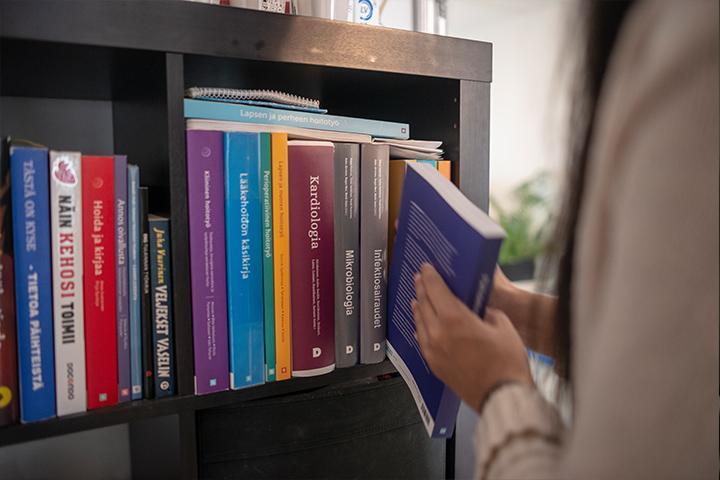 Melissa asettaa kirjaa kirjahyllyyn,