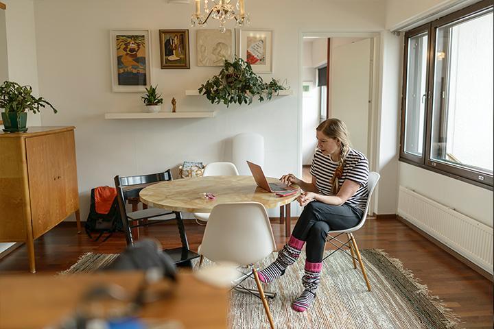 Merja kannettavalla tietokoneella kotonaan pöydän ääressä.