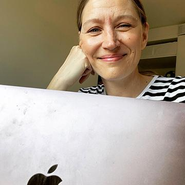 Merja hymyilee tietokoneen takaa.