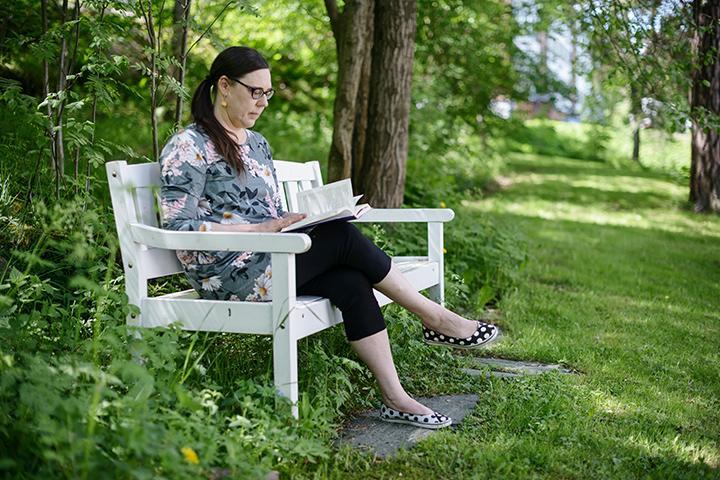 Katja Jokiniemi läser en bok på en parkbänk.