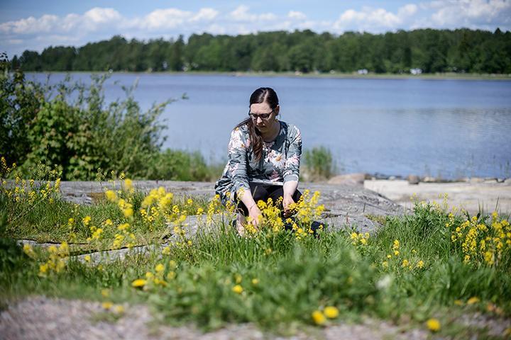 Katja Jokiniemi plockar blommor vid stranden.